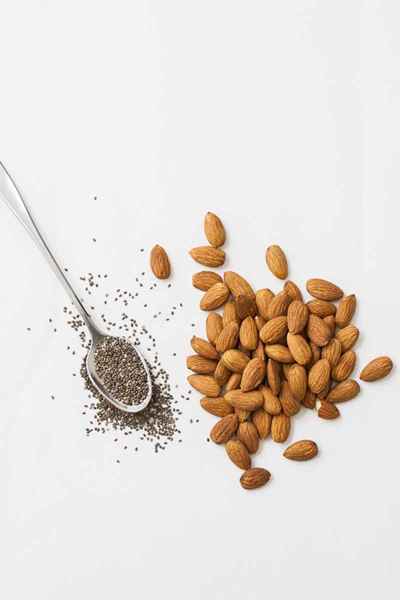 Vertical image of a spoon with chia seeds next to a pile of whole almonds.