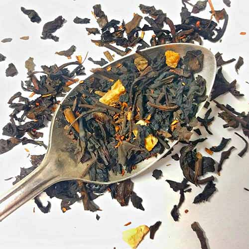 A spoonful of dry loose leaf oolong tea with orange peel on a spoon, with more scattered on a white background.