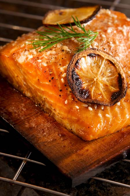 Salmon grilling on wood plank | Fooodal.com