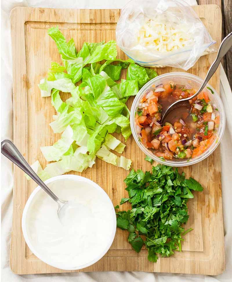 Top down view of the ingredients required to assemble a vegetarian version of a soyrizo taco salad. The ingredients are sitting on a wooden cutting board.