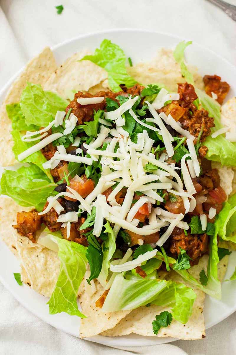 Close up top view of a vegan or vegetarian taco salad made with a bed of tortilla chips, lettuce, black beans, salsa, and cheese.