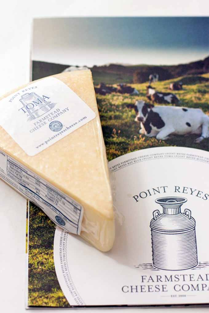 A wedge of Point Reyes Farmstead Toma cheese on top of a pamphlet from the farm with a drawing of a milk jug and a photograph of a black and white cow on the front.