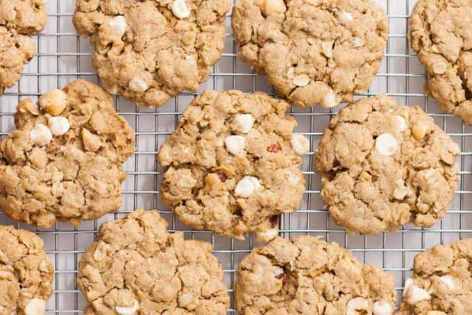 Top down view of a group of vegan white chocolate hazelnut oatmeal cookies placed on a stainless steel cooling rack.