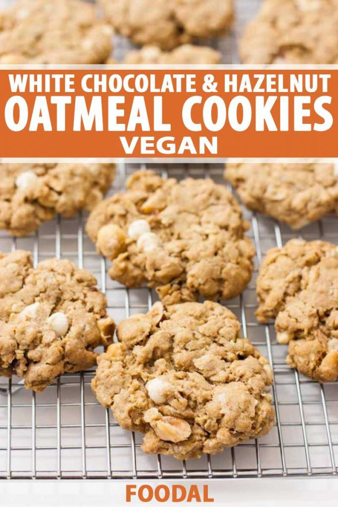 Oblique view of Vegan White Chocolate & Hazelnut Oatmeal Cookies on a cooling rack. Close up.
