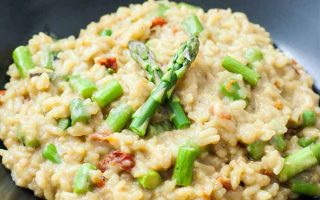 Closeup of a dark gray bowlful of beige-colored vegan asparagus risotto with oven-dried grape tomatoes.