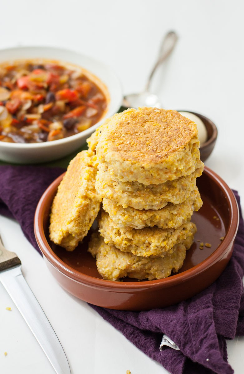 A vertical stack of cornbread skillet biscuits inside of brown, ceramic bowl