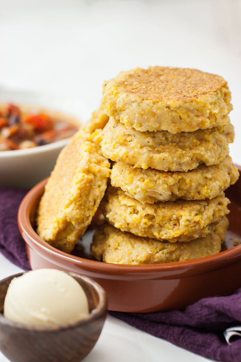 A close up of a stack of cornbread skillet biscuits stacked vertically. A small bowl of non-dairy butter sits next to the stack