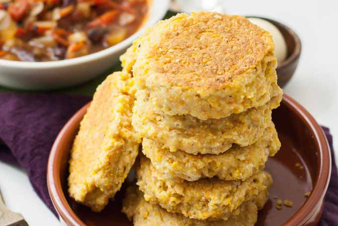 Oblique stack of a vegan-friendly cornbread skillet biscuit recipe stacked inside of a brown, ceramic bowl