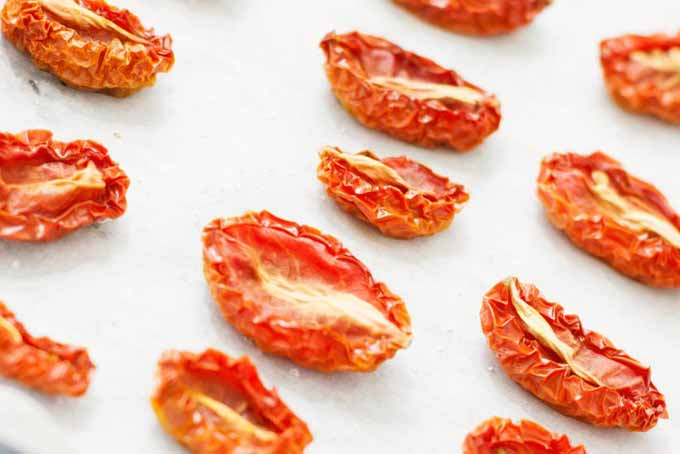 Closeup of three diagonal rows of dried grape tomatoes, with red crinkly edges and white centers, on white parchment paper.