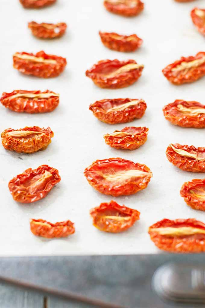 Three vertical rows of shriveled and dry preserved oven-baked tomatoes on a baking sheet topped with a piece of white parchment paper, on a white painted wood surface.