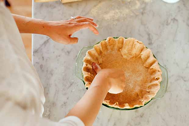 A woman's hands forums a buttered pie crust on a white, marble surface.