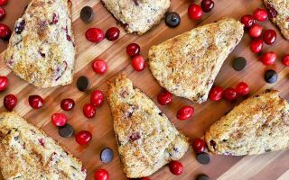Closely cropped overhead shot of seven triangular scones scattered among whole cranberries and chocolate chips on a brown wood surface.