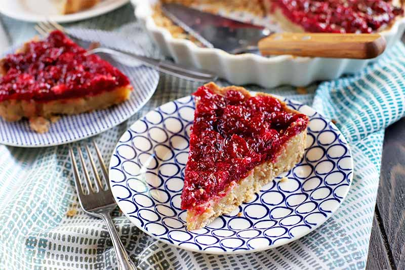 A slice of cranberry and brown butter custard tart is on a black and white patterned plate in the foreground, with another slice and the remainder of the dessert in a white ceramic pie dish in the background, with a metal and wood server, on a cloth surface with a fork.