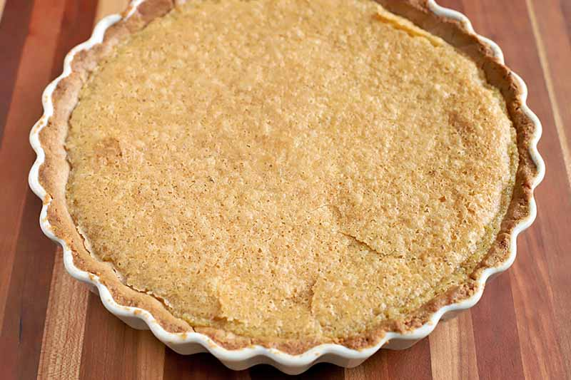 Brown butter custard tart in a white ceramic pie dish with a fluted edge, on a striped wood background.