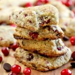 A stack of four scones is in the foreground, with scattered whole cranberries and chocolate chips, and more of the baked goods and fruit in shallow focus in the background, on a wood surface.