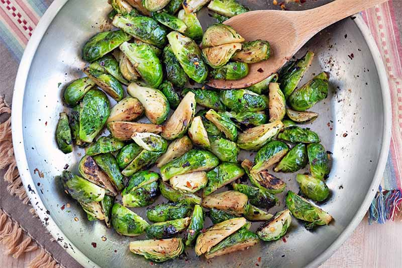 Closely cropped overhead image of a large frying pan of browned Brussels sprouts with spices, and a wooden spoon.