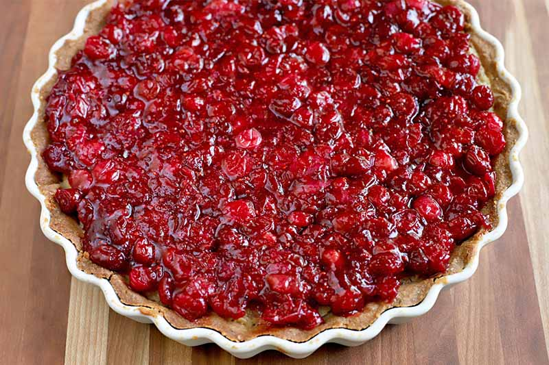 Closely cropped oblique shot of a tart topped with a cooked cranberry mixture, in a white fluted ceramic pan, on a wood surface.
