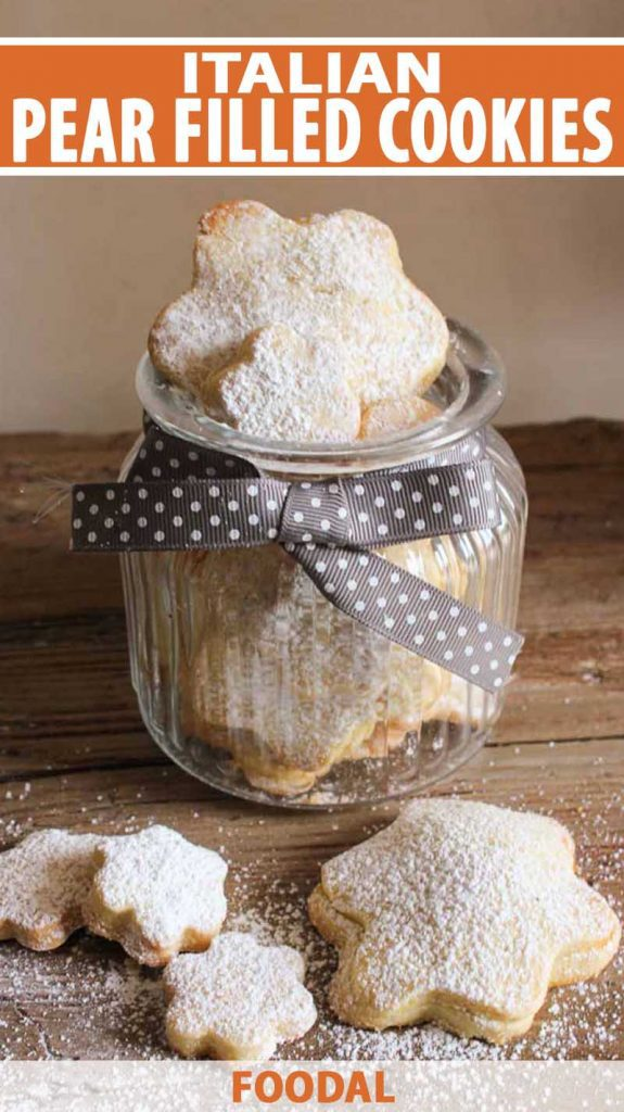 Italian Pear Filled Cookies in a glass jar with other cookies on a wooden table.