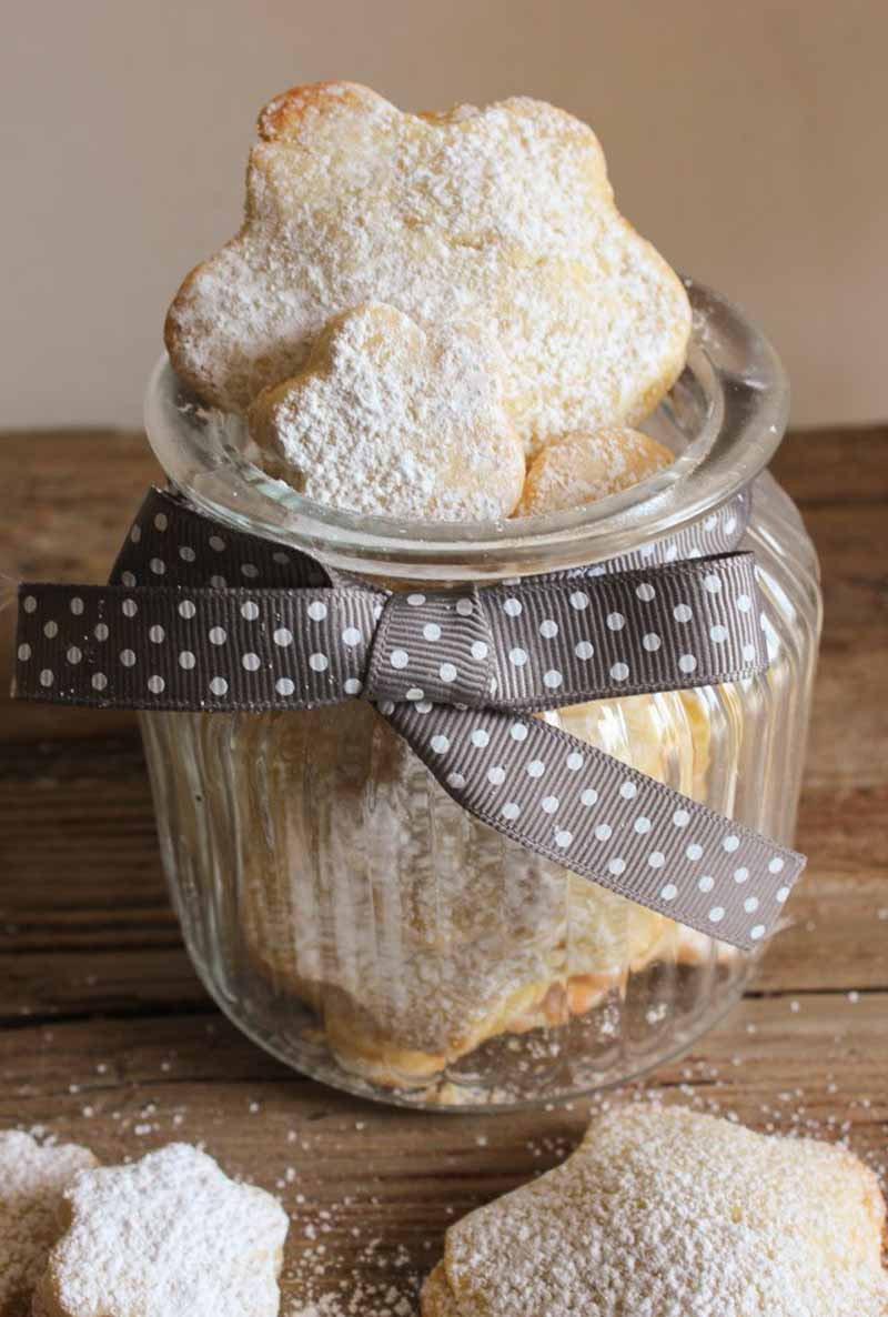 Closeup of a gift jar full of homemade Italian pear filled cookies sitting on a rustic wooden table top.
