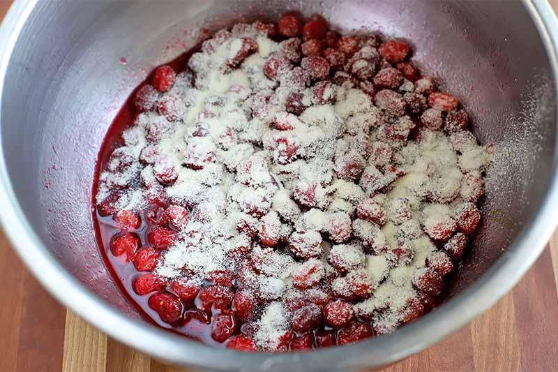 A stainless steel bowl of cranberries dusted with powdered gelatin, on a wood surface.
