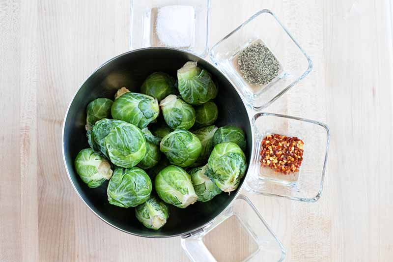 Top-down shot of a large stainless steel mixing bowl of whole raw Brussels sprouts to the left of the frame, with four small square glass dishes of salt, ground black pepper, red pepper flakes, and coconut oil arrananged around the right half of the bowl, on a beige countertop.
