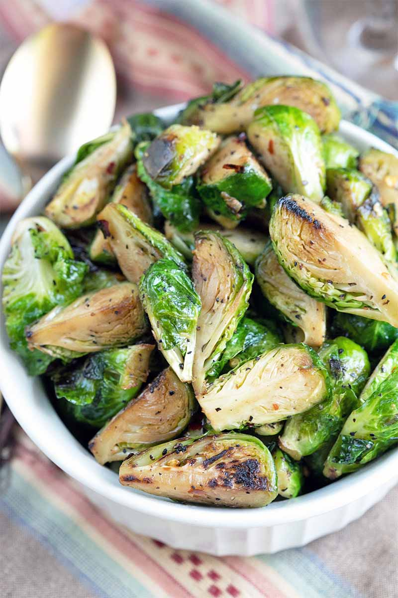 Oblique overhead shot of a white serving dish filled beyond the brim with caramelized Brussels sprouts, with a metal serving spoon in shallow focus in the background, on a cloth surface.