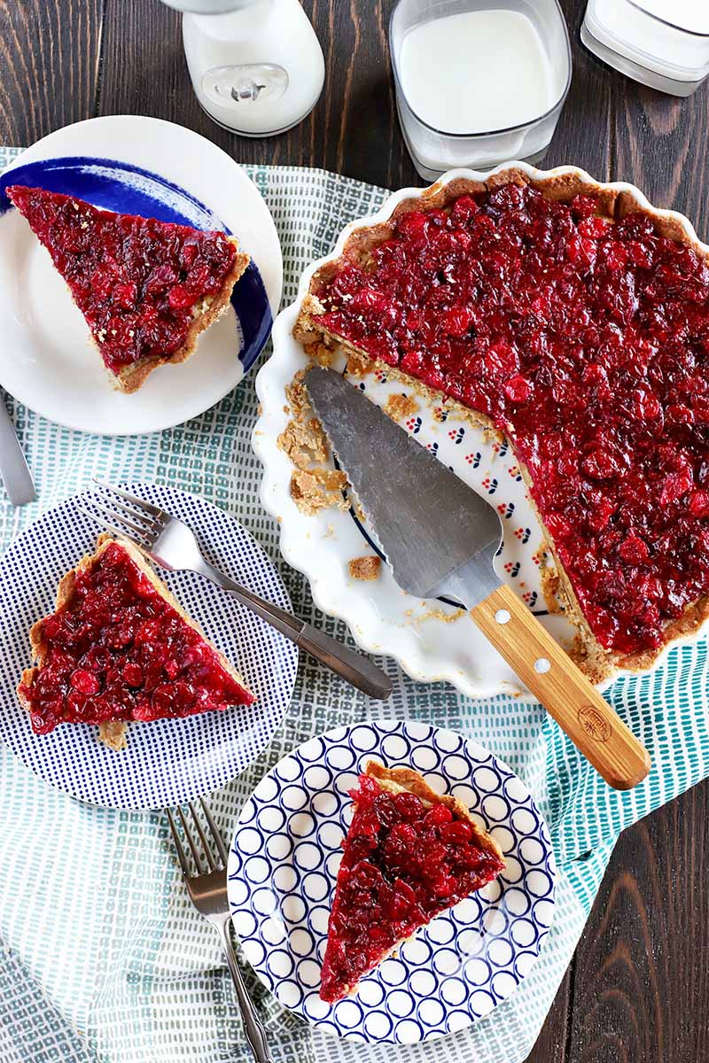Overhead shot of three dessert plates with slices of cranberry tart, with the remainder of the dessert in a fluted ceramic pie dish to the right, with a metal and wood pie server in the empty space in the pan, on a cloth surface.
