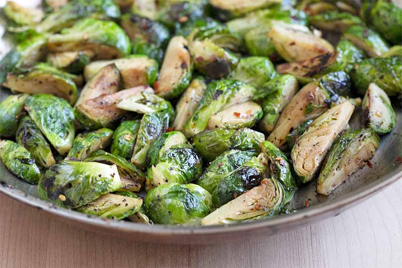 Sauteed Brussels sprouts with red chili, in a large frying pan.