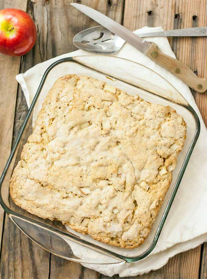 Overhead shot of a square glass baking dish of vegan apple cake, on a folded white cloth with a slotted serving spoon and a serrated knife with a wood handle, with a red and green apple on a brown unfinished wood surface.