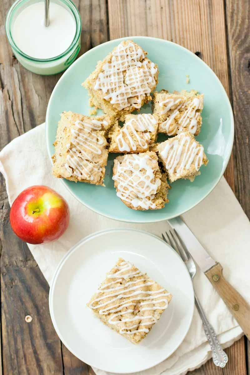 Vertical overhead shot of a pale green plate and a white dessert plate of roughly square slices of vegan apple cake topped with a drizzle of white icing, with a red and yellow apple, a green glass of almond milk, a white cloth, a fork, and a wood-handled knife, on a rustic unfinished wood background.