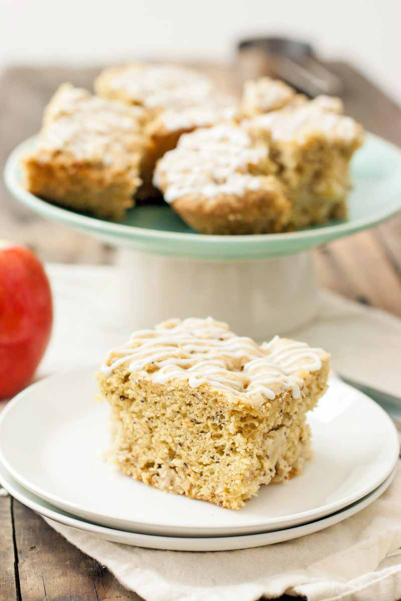 A slice of vegan apple breakfast cake on a stack of two small white plates in the foreground, with more on a pastel green and white ceramic cake stand in the background, with a whole apple and a white cloth on a brown surface, against a white backdrop.