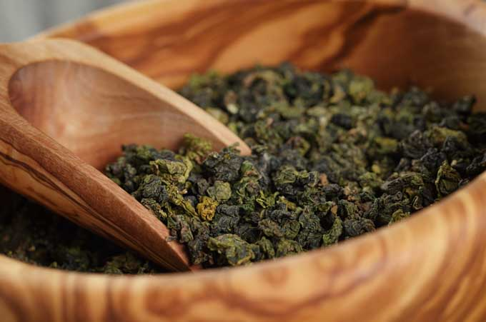 Wooden bowl full of oolong tea leaves |