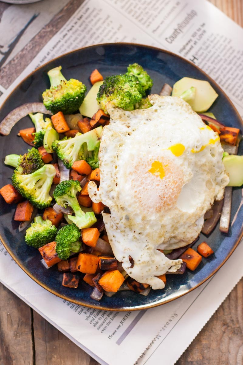 Top-down view of an over-easy egg on top of a sweet potato and broccoli hash.