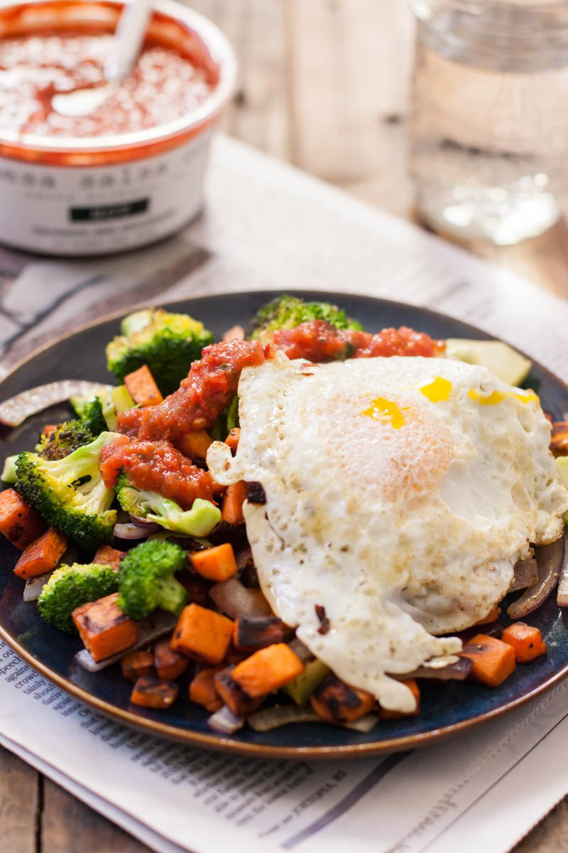 Oblique view of an over easy egg over the top of sweet potatoes and broccoli on a black porcelain plate. A container of salsa is in the background.