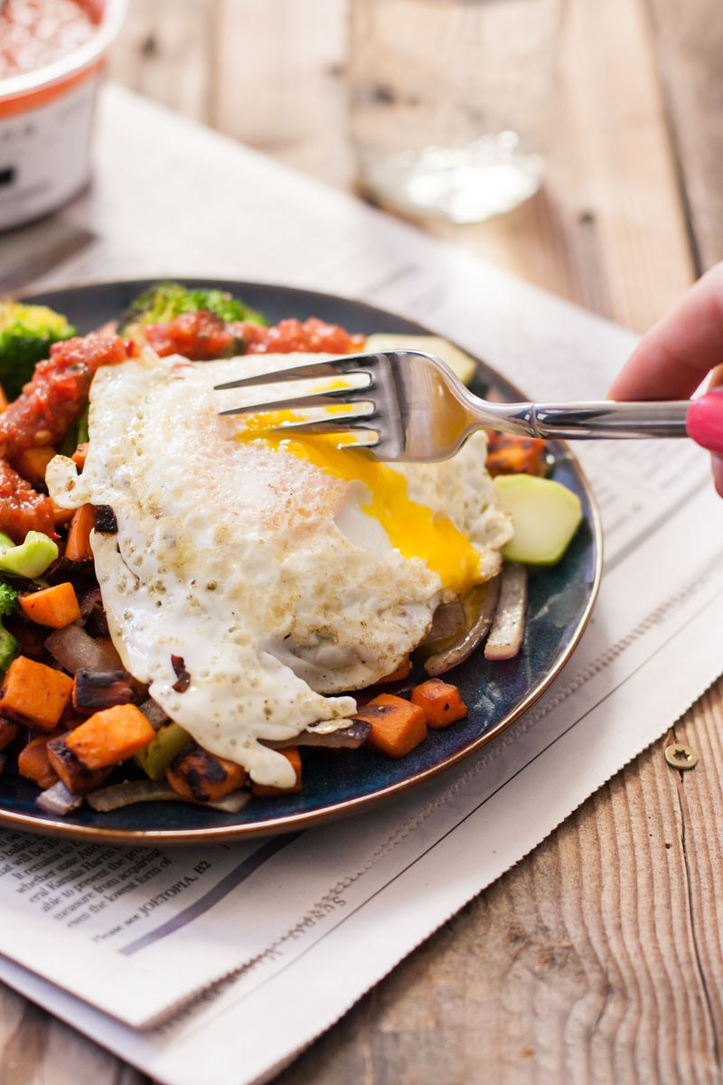 Oblique view of a hand using a fork to burst the yolk of an over-easy egg  the top of a sweet potato and broccoli hash.