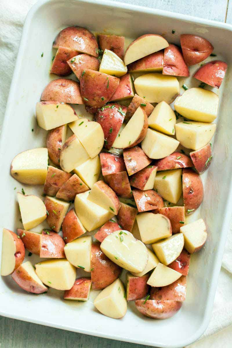 Overhead shot of a white rectangular baking dish filled with chopped red-skinned potatoes.