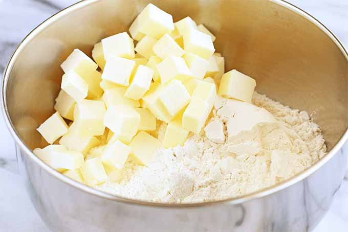 A stainless steel mixer bowl of cubed butter and flour, on a marble background.