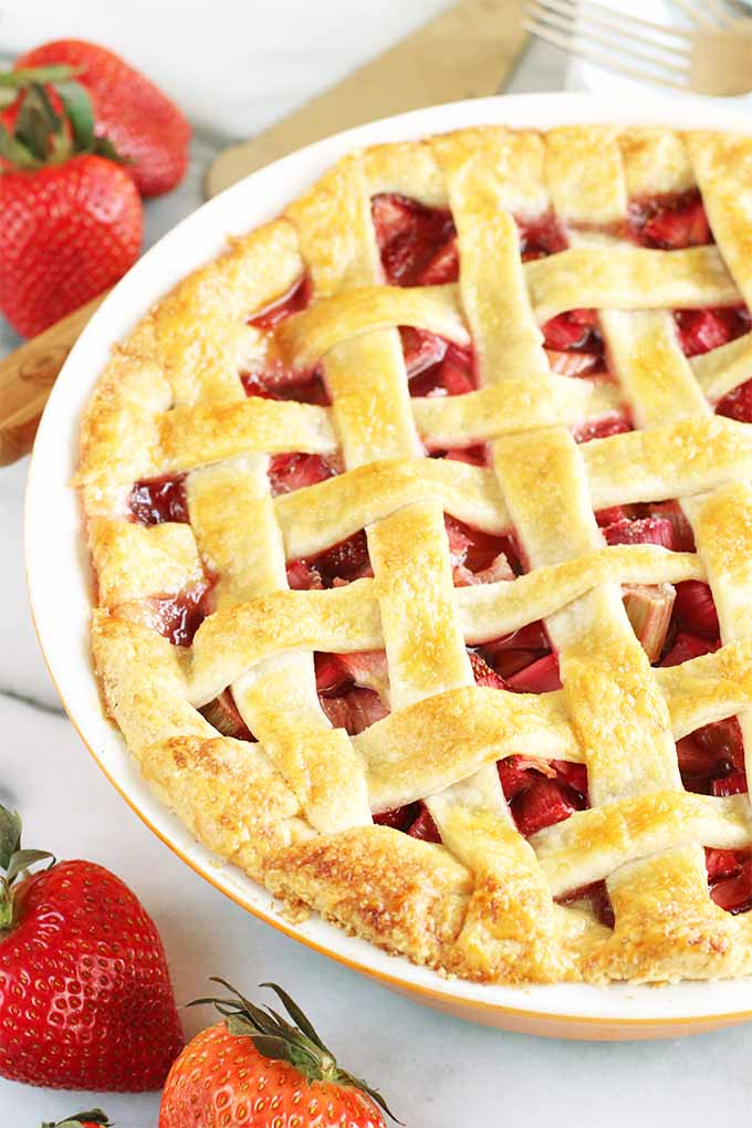 A strawberry rhubarb pie with a lattice top crust in a white ceramic pie dish, on a marble background with scattered whole strawberries, and a wood and silver metal pie server.