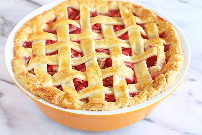 A just-baked strawberry rhubarb pie with a golden brown buttery lattice crust top, on a marble background.