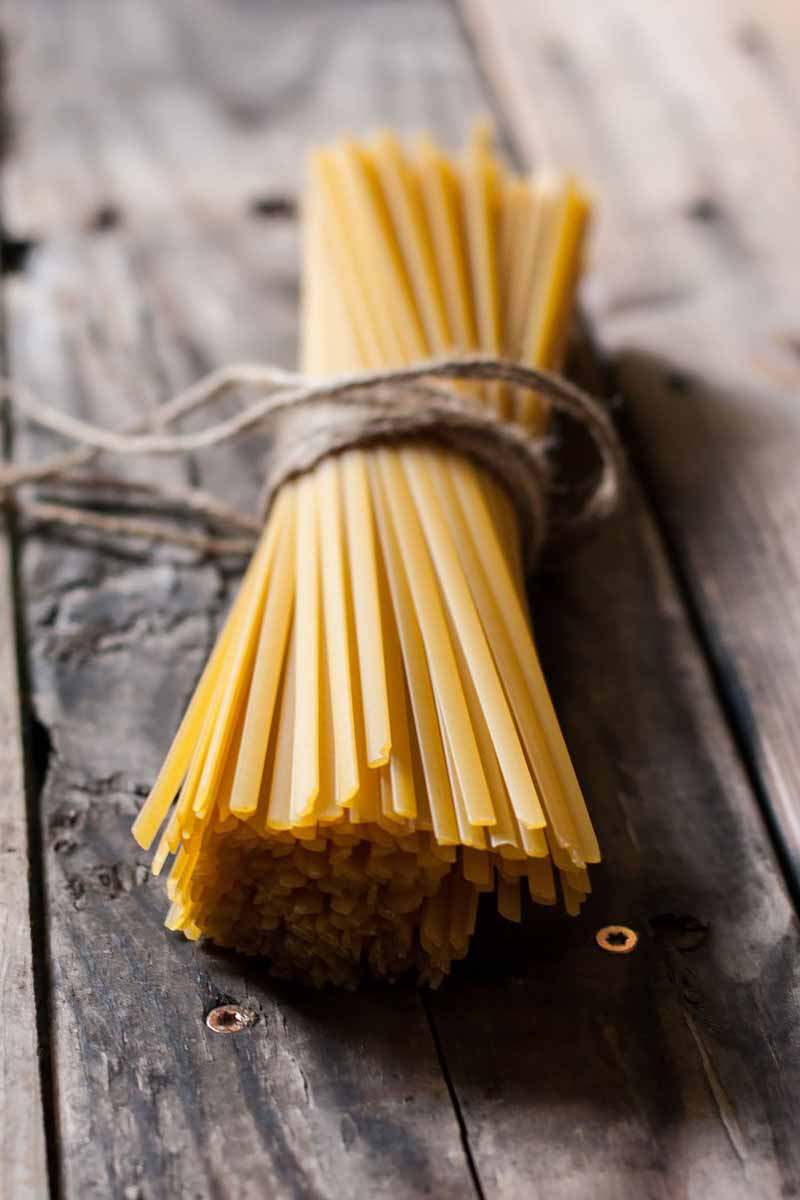 Vertical image of a bundle of uncooked pasta on a wooden surface.
