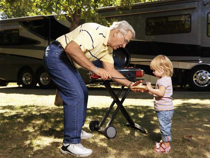Grandfather and grandaughter grilling by the RV | Foodal.com