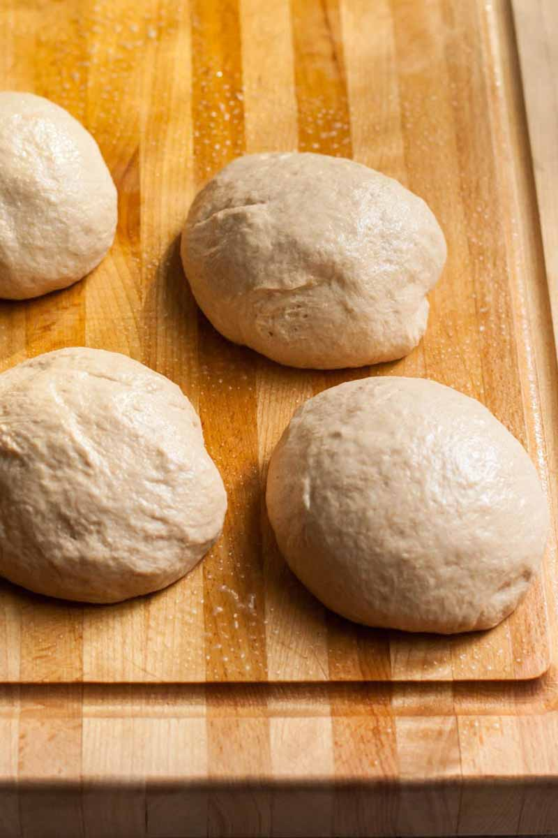 Four round balls of pizza dough on a wooden cutting board.