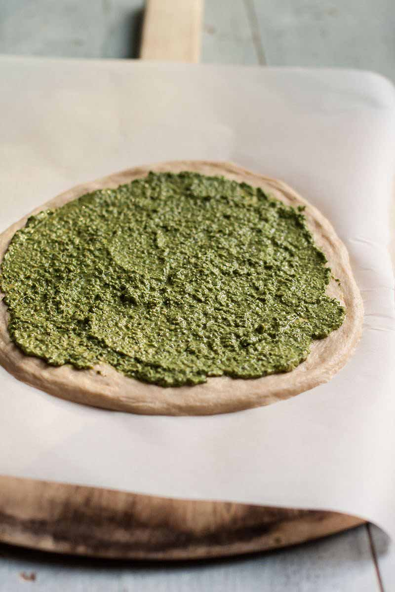 Raw pizza dough on parchment paper with a coating of pesto smeared across the top.
