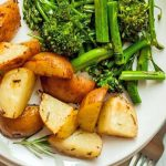 Overhead closely cropped shot of a white plate of red-skinned roasted potatoes and sauteed broccolini, with a fork.