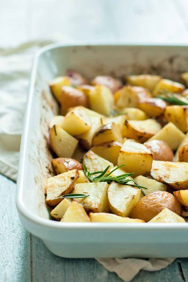 Roasted potatoes with rosemary in a white ceramic baking dish, on a white surface topped with an off-white cloth.