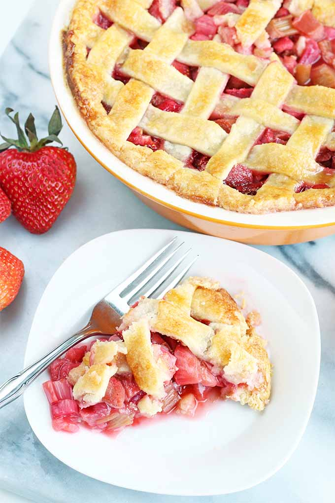 A piece of strawberry rhubarb pie with a lattice top crust is on a square white dessert plate with a silver fork in the foreground, with the rest of the dessert in an orange and white ceramic dish in the background, on a gray and white marble surface with a few whole strawberries.