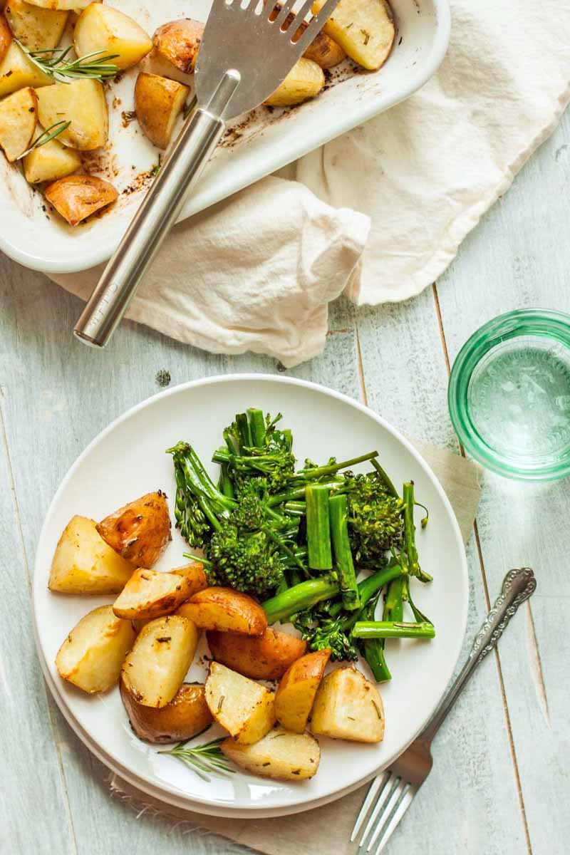 Overhead shot of a baking pan and a plate of roasted potatoes, with a metal serving utensil, a fork, sauteed broccolini, and a green glass, on a wrinkled and folded white cloth, on a plain whitewashed wood background.