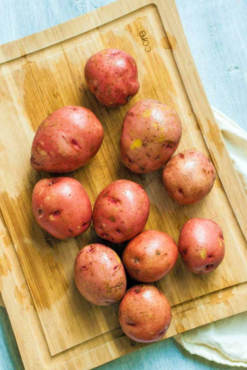 Overhead shot of ten red-skinned potatoes on a wet wooden cutting board arranged at an oblique angle, on a white surface.
