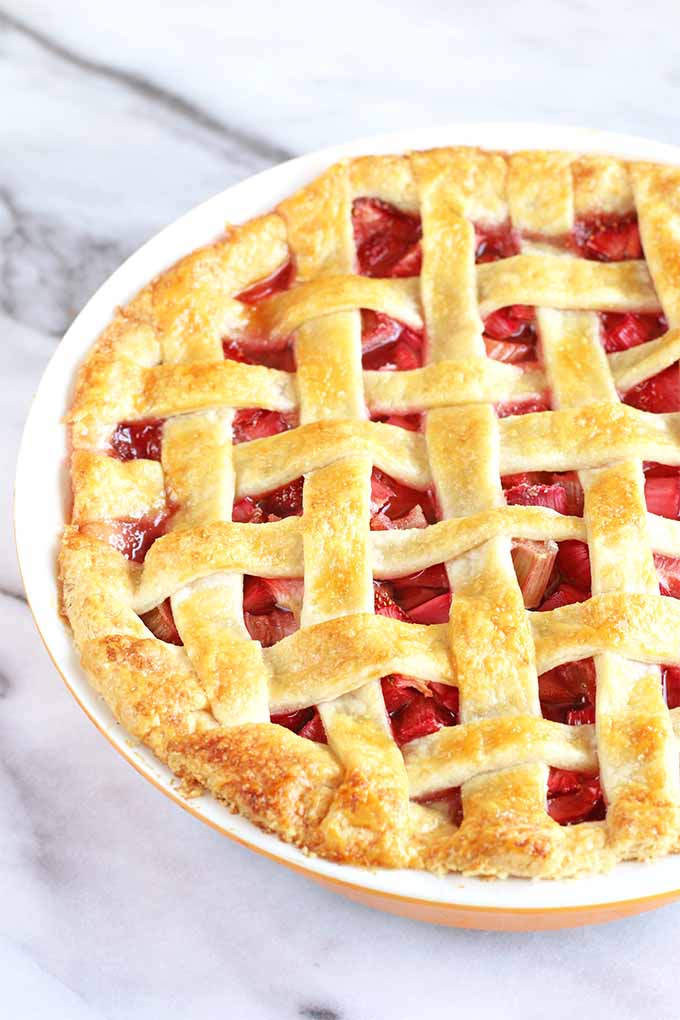Closely cropped image of a lattice-topped strawberry rhubarb pie with a golden brown crust, on a white and gray marble background.