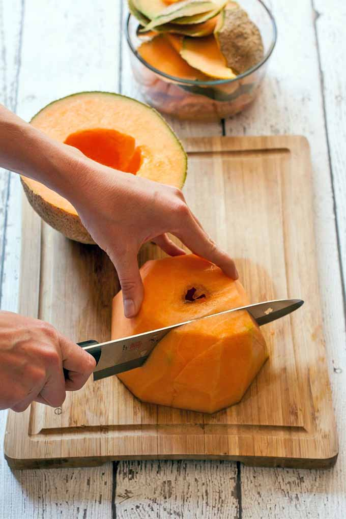 Closeup of a hand holding half of a cantaloupe down on a cutting board while the other hand slices into it with a chef's knife, beside a small glass bowl that is being used to collect the rinds, on a wood table.